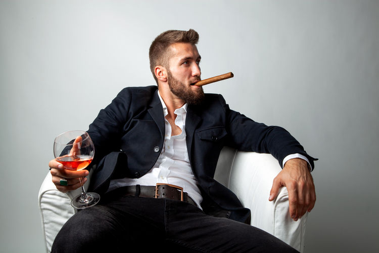 Attractive bearded man with a cigar, and a glass of whiskey in his hands is sitting in a white armchair Sitting Glass Indoors  Drink Front View Adult Men Beard Businessman Cigar Whiskey Suit Lifestyles Career Relaxing Armchair Males  Guy Hand Holding Stylish Success Smoker Bad Habit Tobacco