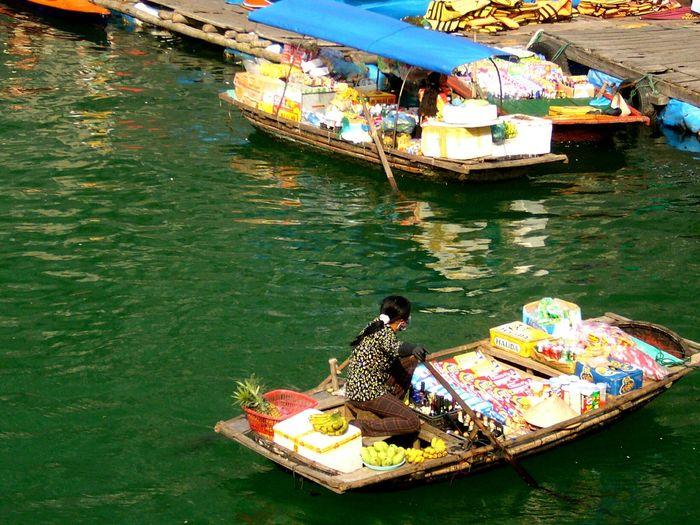 Female vendor rowing boat at floating market