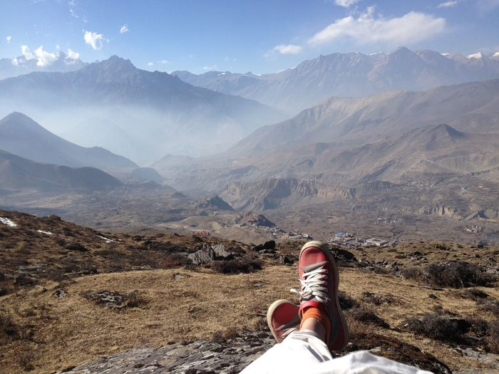 Low section of person sitting on mountain against sky