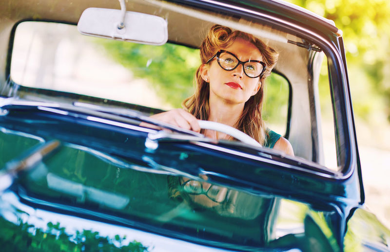 Beautiful happy woman sitting in a car. Retro styled Automobile Blonde Driver Summertime Transportation Woman Attractive Auto Beautiful Woman Caucasian Driving Around Eyeglasses  Eyewear Headshot Looking At Camera One Person Outdoors People Retro Car Retro Styled Serious Summer Vintage Cars Young Adult Young Women