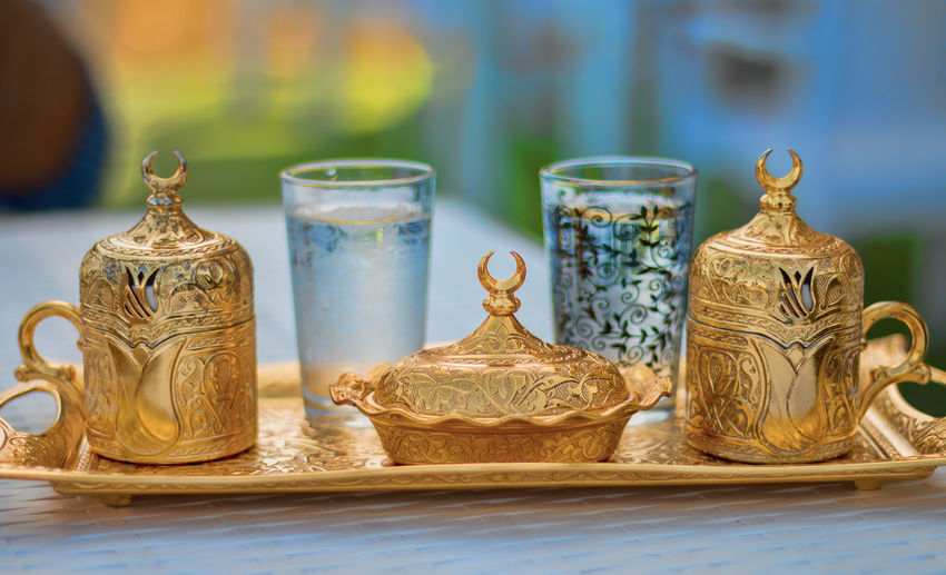 Close-up of gold colored teapots and drinking glasses in tray on table