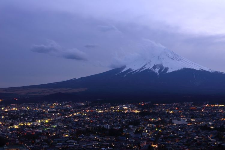 High angle view of illuminated cityscape by mount fuji at night