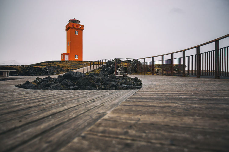 Surface level of lighthouse by sea against sky