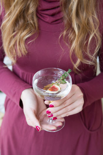 Midsection Of Woman Having Drink In Glass