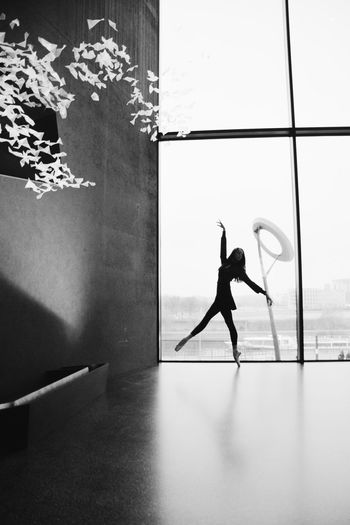 Digital composite image of silhouette woman standing by window