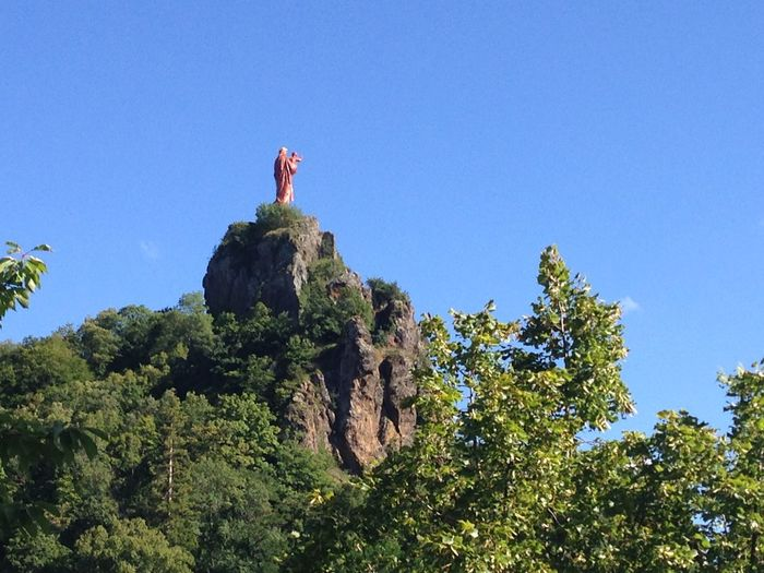 Our Lady of Le Puy Beauty In Nature Blue Clear Sky Copy Space Day Freedom Full Length Green Color Growth Leisure Activity Low Angle View Mountain Nature Our Lady Our Lady Of Le Puy Outdoors Rock - Object Rock Formation Sky Sunlight Tree