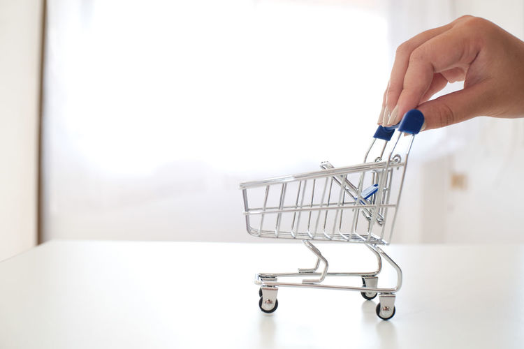 Close-Up Of Woman Hand Holding Miniature Shopping Cart On Table