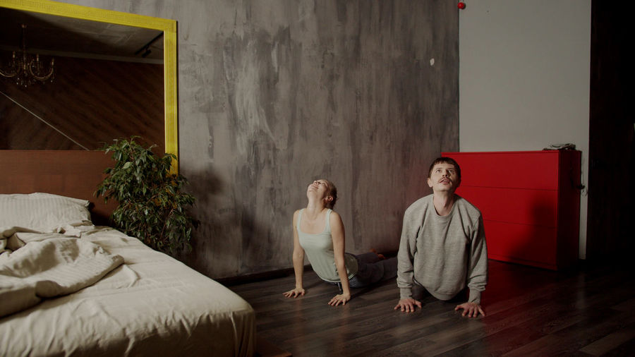 Couple exercising on floor at bedroom