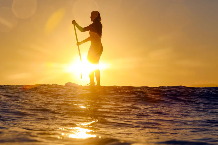 Silhouette woman on sea against sky during sunset