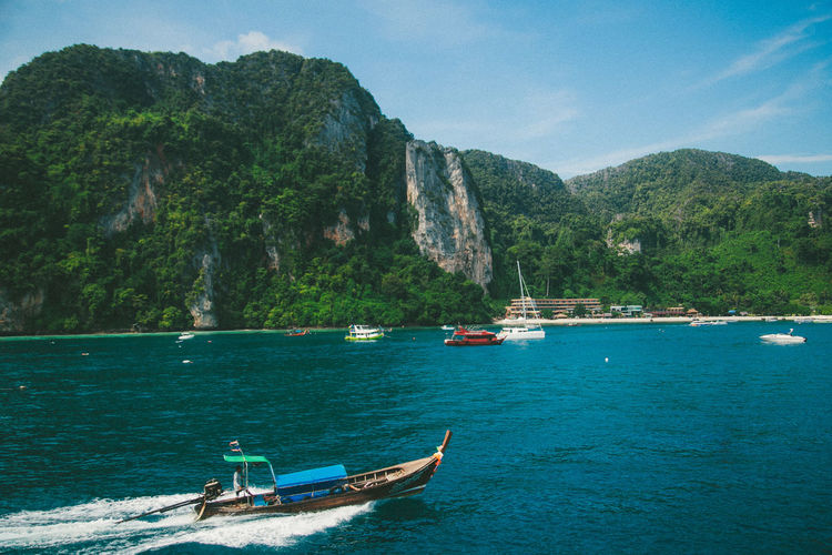 Boats sailing in sea by phi phi island against sky