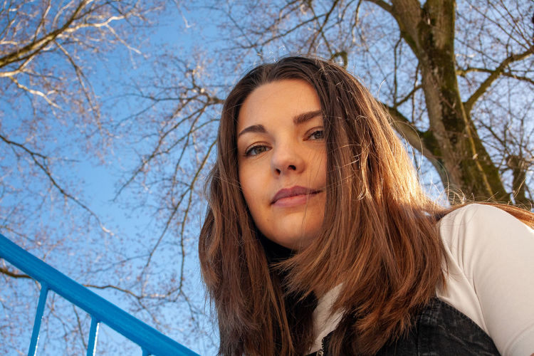 Portrait of young woman against bare tree