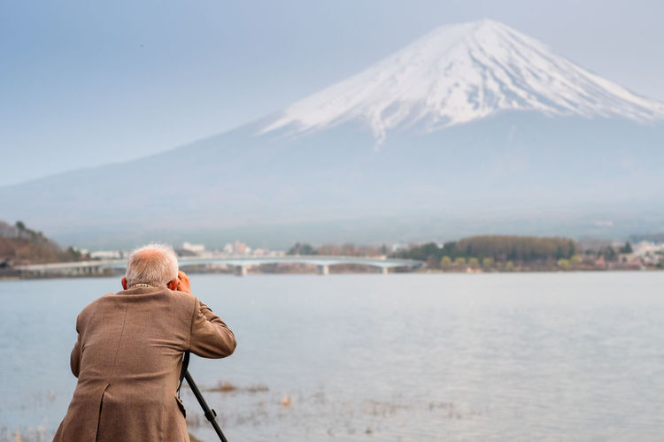Rear view of senior man photographing by lake