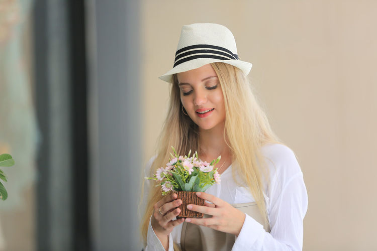 Portrait of a beautiful young woman holding white flower