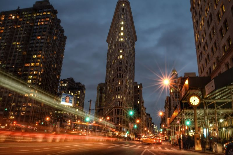 Light trails on road by flatiron building at night