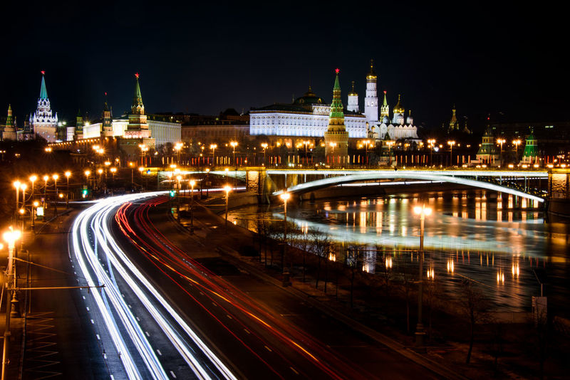 """When we say """"Kremlin"""", we immediately think about Moscow Kremlin and the word is often used as a synonym for """"the Russian government"""", as this is where the country's president has his office. In reality, in Russian Kremlin (Кремль) means """"fortress"""" or """"citadel"""" and many old Russian cities and towns have their own kremlin. It is a fact, on the other hand that the Moscow Kremlin is in many aspects the hearth of the hole country. First of all, the site has been continuously inhabited by Finno-Ugric peoples since the 2nd century BC. The Slavs occupied the south-western portion of Borovitsky Hill (or Kremlin Hill) as early as the 11th century, as evidenced by a metropolitan seal from the 1090s which was unearthed by Soviet archaeologists in the area. The word """"Kremlin"""" was first recorded in 1331. In the second half of the XV century, Grand Prince Ivan III organised the reconstruction of the Kremlin, inviting a number of skilled architects from Renaissance Italy, including Pietro Antonio Solari, who designed the new Kremlin wall and its towers, and Marco Ruffo who designed the new palace for the prince. It was during his reign that three extant cathedrals of the Kremlin, the Deposition Church, and the Palace of Facets were constructed. The highest building of the city and Muscovite Russia was the Ivan the Great Bell Tower, built in 1505–08 and augmented to its present height in 1600. The Kremlin walls as they now appear were built between 1485 and 1495. This 600-year-old red fortress is a sight to behold and I think that at night it is spectacularly illuminated. When the sky is overcast the clouds over Moscow reflect the light from the bustling metropolis below, often turning a strange purplish hue, but on clear nights you can still get an excellent tonal separation between the brightly light white buildings and the dark sky. The red stars atop the various towers are also illuminated and they stand up beautifully, I think. Cityscape Downtown Kremlin Moscow Russia Travel P"""