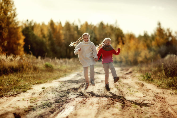 Two sisters in warm sweaters hug and run along the trail in the autumn forest. happy children