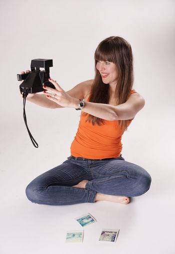 Eine junge Frau sitzt barfuß auf dem Boden und macht mit einer Polaroidkamera ein Selfie. Sie fotografiert sich selbst. Barefeet Barfuß Barfußpark Casual Clothing Fotografieren Fotografieren Im Wald Fotos Machen Frau Fun Füsse Jeans Kamera Looking At Camera Oldschool Perspective Photography Polaroid Polaroid Camera Polaroidcamera Polaroidkamera Polaroids Selfie Young Adult Young Women