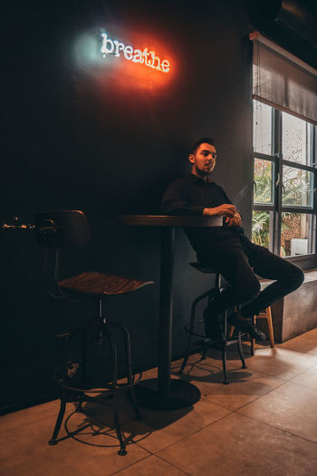 the man in black sits alone in a room Seat One Person Real People Sitting Chair Full Length Illuminated Indoors  Business Communication Lifestyles Casual Clothing Table Text Front View Men Lighting Equipment Leisure Activity Young Adult Contemplation Cafe Cafe Time Room Room Decor