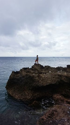Man on rock by sea against sky