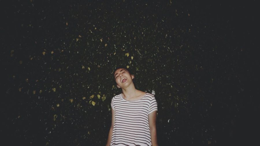 Cheerful young woman standing against plants at night