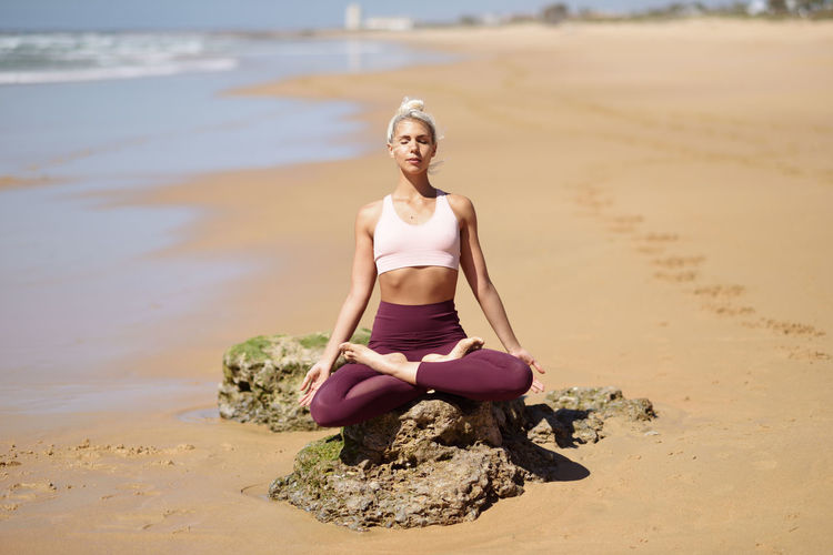 Full length of young woman meditating while sitting at beach during summer