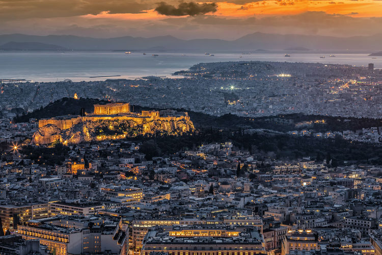 View over the skyline of Athens, featuring the Parthenon Temple at the Acropolis, just after sunset, Greece Architecture Building Exterior Sky City Built Structure Sunset Aerial View Illuminated Cloud - Sky Travel Destinations High Angle View Orange Color Outdoors Building Cityscape Athens Greece Acropolis Mediterranean  Greek Parthenon Evening Landmark Sea Urban