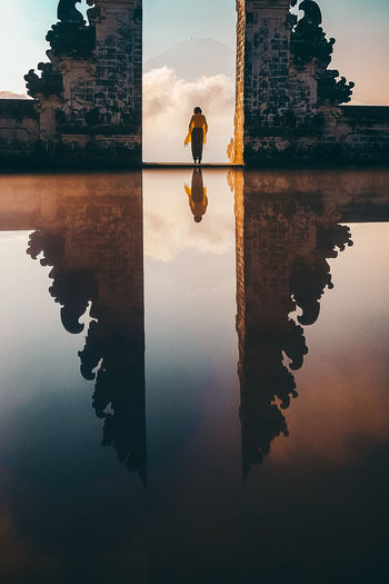 Reflection Of Woman Amidst Built Structure On Lake Against Sky