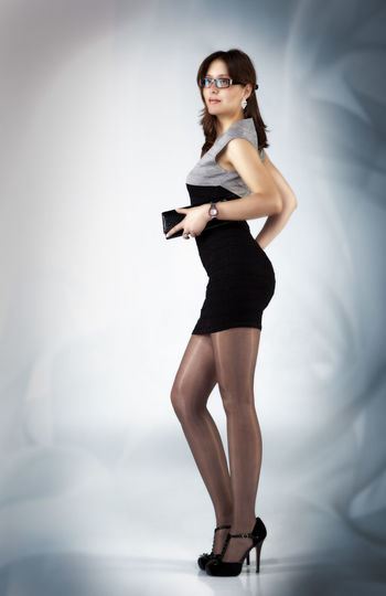 Full Length Of Beautiful Woman Standing Against Gray Background