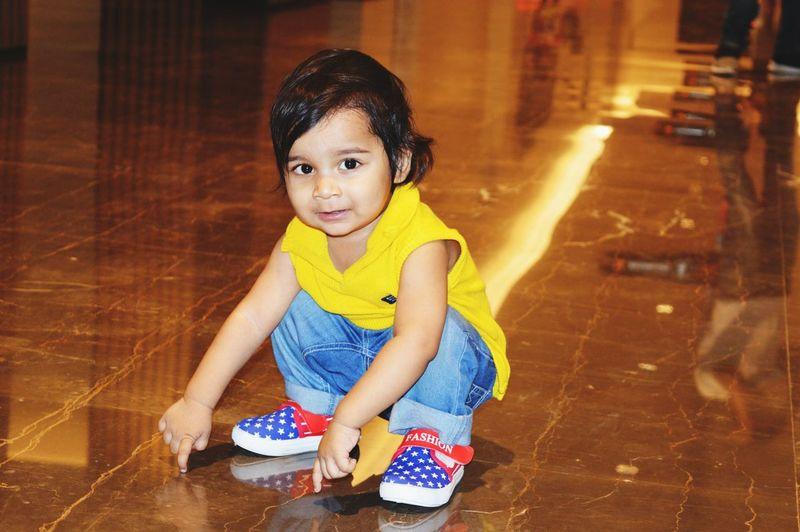 Portrait of cute girl sitting on wooden floor