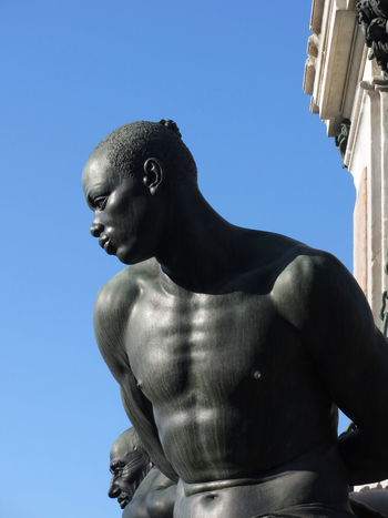 The monument Quattro Mori ( of the Four Moors ) in Livorno city . View of one of the four moors against the blue sky . Tuscany, Italy African ArtWork Bandini Bronze Four Livorno Medici Renaissance Square Statue Tacca Tuscany Art Black Chain Historic Italy Monument Moors Mori Muscle Sculpture Slave Tourism Town