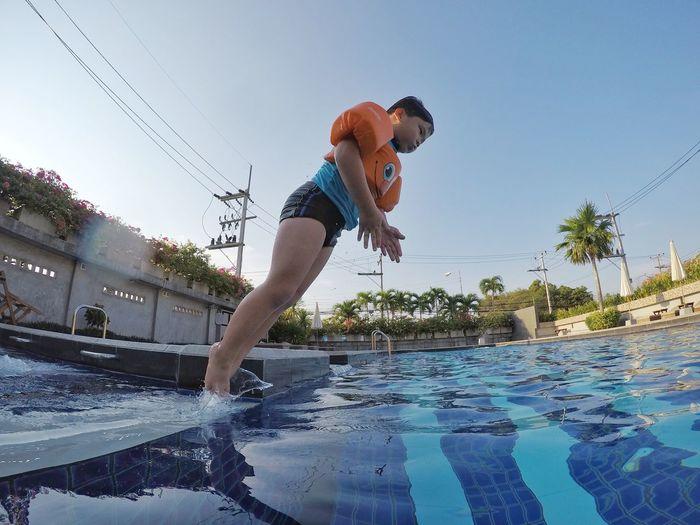 People in swimming pool against sky