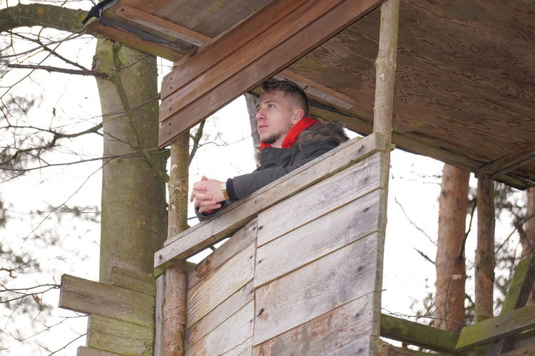 Low angle view of man in small wooden house in forest