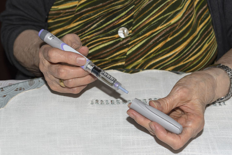 Diabetic old lady preparing her insulin pen to inject her dose. Health concept. Diabetic Insulin Dosis Injection Glucose Treatment Hospital Health Care Medication Injector Hypodermic Needle Patient Vial Pen Old Lady Illness Background Wallpaper Copy Space Concept Therapy Prescription