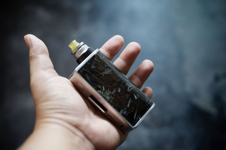 Close-up of cropped hand holding electronic cigarette