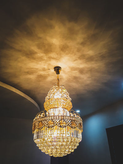 Low angle view of illuminated chandelier against sky