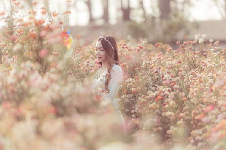 Woman standing by flowering plant