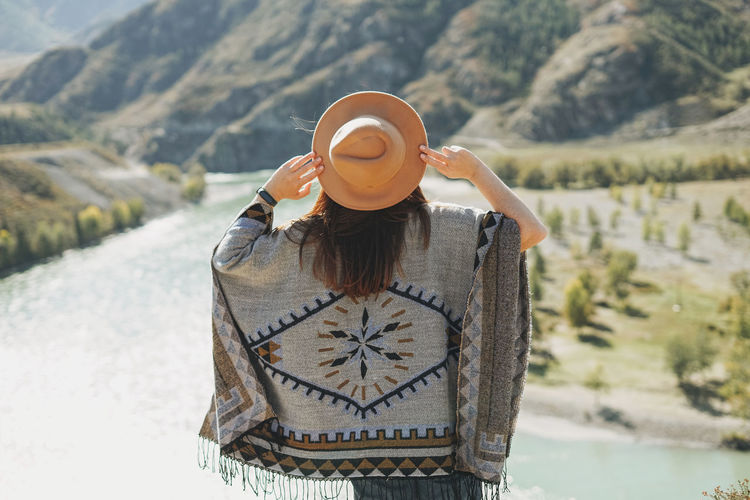 Carefree brunette young woman traveler in poncho from back on background of mountain river