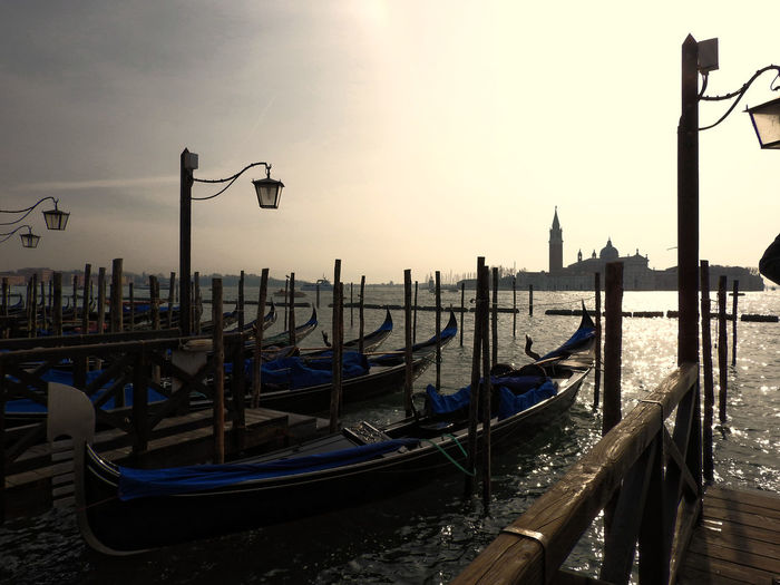 Gondolas at grand canal against sky in city