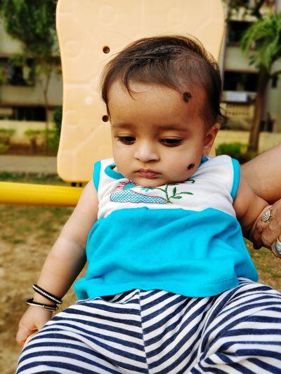 Cute Baby Girl Sitting In Park