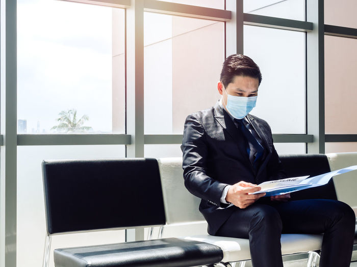 Businessman wearing mask holding document sitting in office
