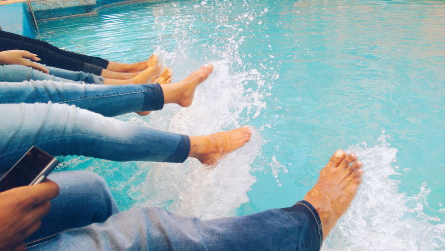 People sitting by swimming pool