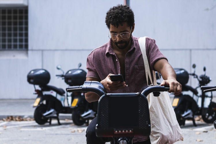 Young man using mobile phone while sitting on motorcycle