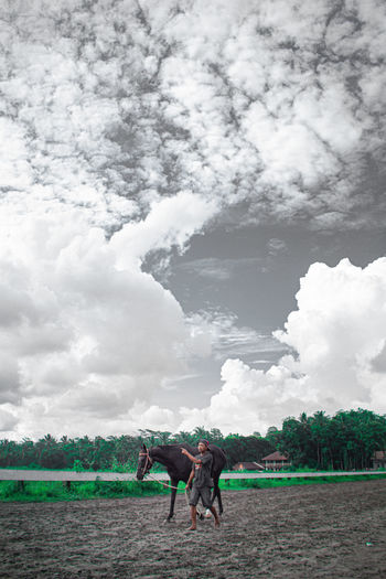 People riding horse on field against sky