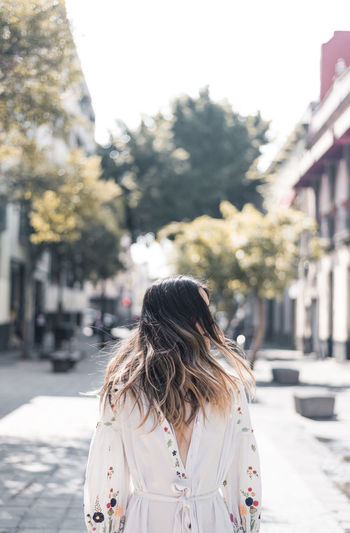 Heart full of soul. Adult Architecture Building Exterior Built Structure City Day Focus On Foreground Lifestyles Long Hair One Person Outdoors People Real People Rear View Sky Street Sunlight Tree Women