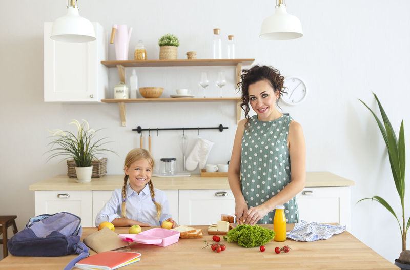 Portrait of smiling mother preparing food at kitchen with daughter