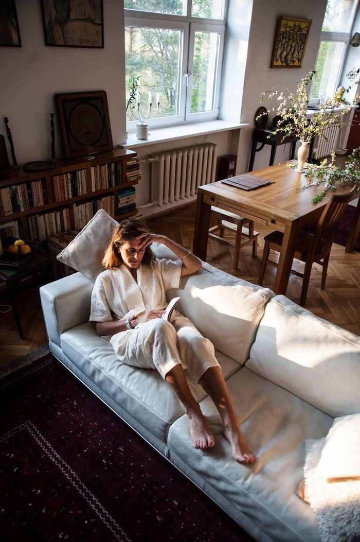 YOUNG WOMAN SITTING ON SOFA IN LIVING ROOM