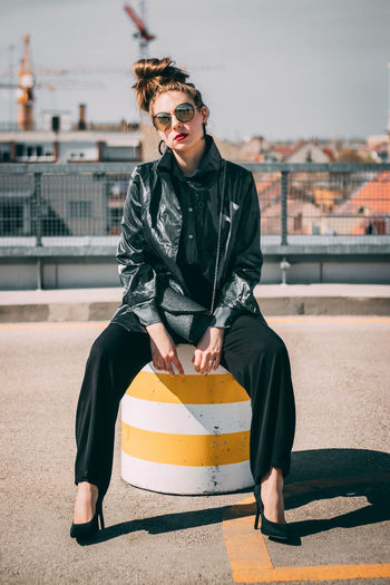 Portrait of fashionable woman wearing sunglasses while sitting in city