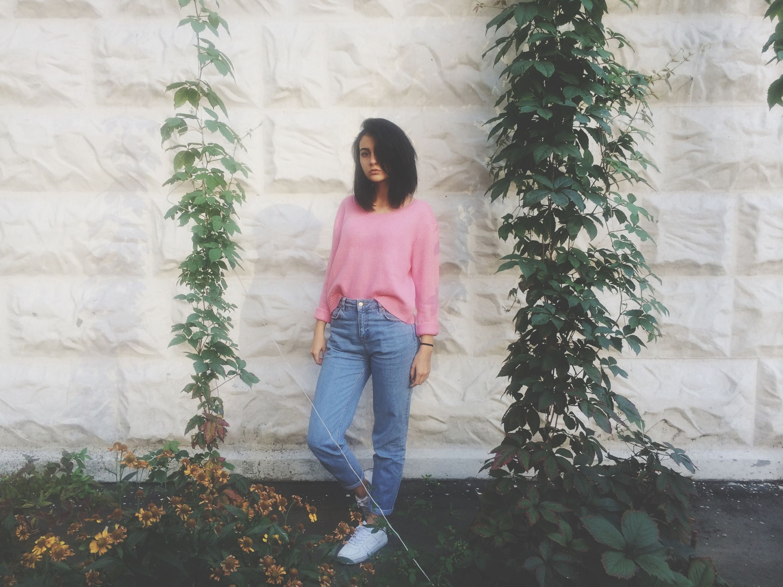 standing, lifestyles, casual clothing, wall - building feature, young adult, plant, young women, leisure activity, full length, three quarter length, person, front view, architecture, built structure, wall, growth, day