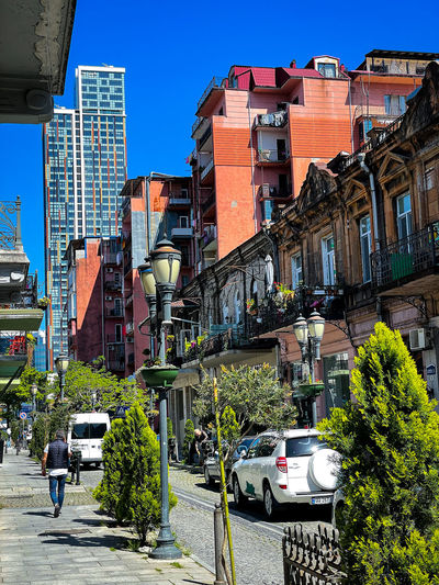 Street amidst buildings in city against clear sky