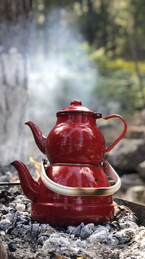 Close-up of kettle with teapot on campfire